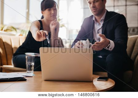 Woman Presenting Business Idea On Laptop To Businessman