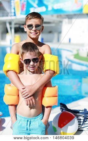 Boys with Arm Floaters Standing by the Pool