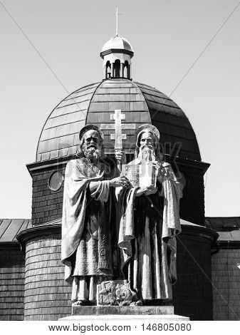 Religious statue and wooden chapel of Saint Cyril and Methodius on Radhost Mountain in Beskids, aka Beskydy, Czech Republic . Black and white image.