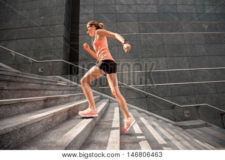 Young sports woman running down the stairs in the modern city. Healthy lifestyle and morning jogging in the city