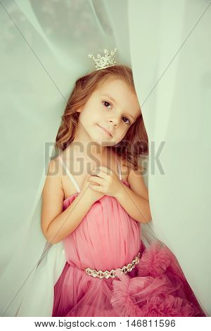 Portrait of cute little girl with hands on chest in pink dress and diadem looking at camera