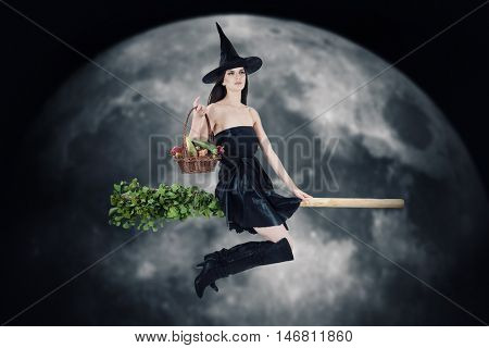 Young woman dressed as a witch carrying vegetable basket and riding a broom. Blurred moon in background.
