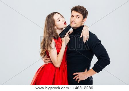 Sensual young couple playing and posing with gun