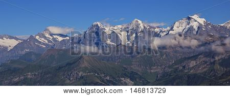 Famous mountains Eiger Monch and Jungfrau in summer. View from Mt Niesen. Swiss Alps.