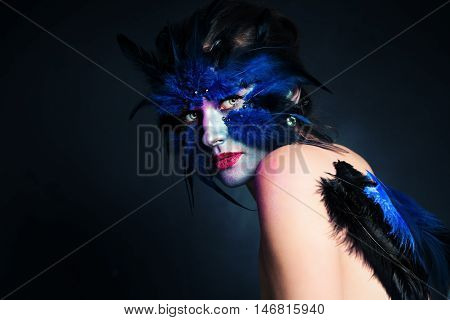Halloween Makeup. Fantasy Bird Woman with Artistic Make-up on Blue Background and Copy space for Text
