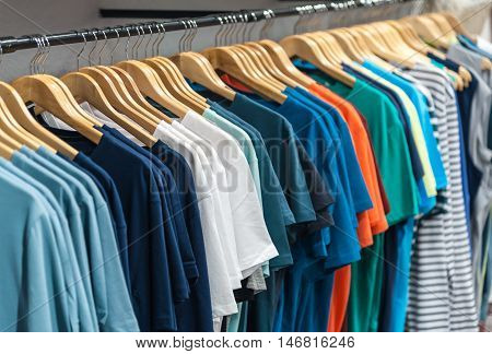 Many colorful t-shirt hanging in a wardrobe