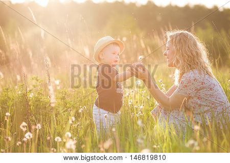 Cute little toddler boy in a straw hat holding his mother's hand and blowing dandelion. Adorable child walking with his mom in park on sunny summer day. Family on sunset. Childhood motherhood concept