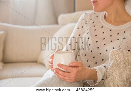 Girl with coffee mug sitting on the sofa indoors. Woman drinking a cup of coffee or tea sitting cozy at home. Relax and rest.