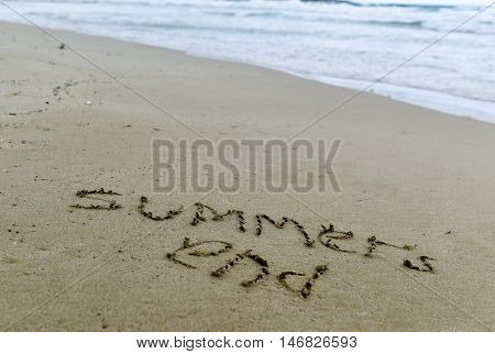 closeup of the text summers end carved in the sand of a beach