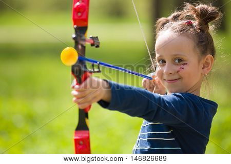 Cute girl archer with bow shooting in sunny summer day. little girl shoots bow in the park. Outdoors. Sport activities with children. Sport and lifestyle concept. Aiming high