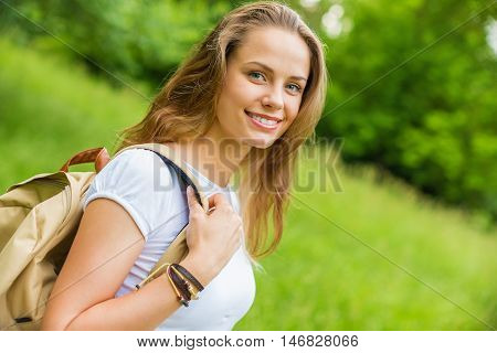 Student girl outside in summer park smiling happy. Asian female college or university student. Mixed race Asian / Caucasian young woman model wearing school bag