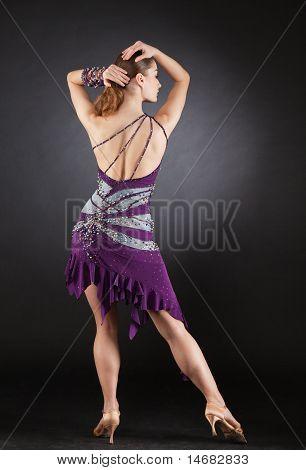 Back shot of dancing girl in violet dress studio isolated image poster