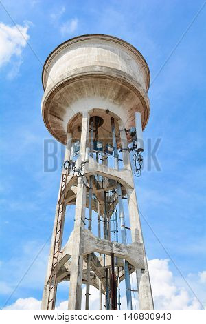 Spotlight and cell phone antenna on water tank tower with blue sky and cloud background.