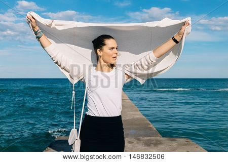 Young Brunette In A Cardigan And Skirt Standing On A Pier In The Background Of The Sea And Enjoys A