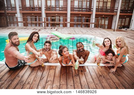 Croup of cheerful happy friends drinking beer at the pool outdoors