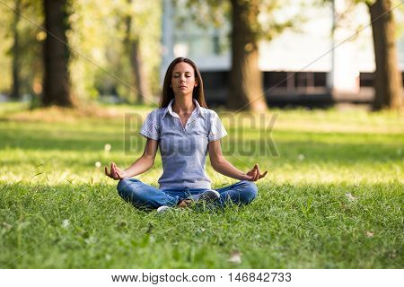 Beautiful businesswoman is resting from work at the park and meditating.