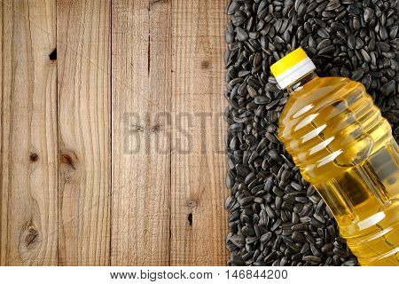 Sunflower seeds and bottle of sunflower oil on wooden background