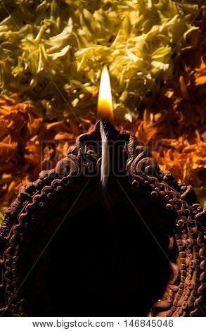 Traditional diya or oil lamp lit on colorful rangoli made up of flower petal, on the festival of lights called diwali or deepawali, selective focus