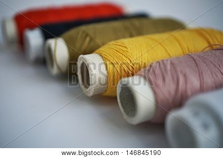 Set of spools with colorful threads used for sewing as a symbol of housework, needlework and handwork