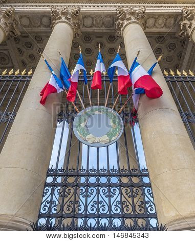 French flags on a historical building - Antique building close up decorated with french flags in Paris France.