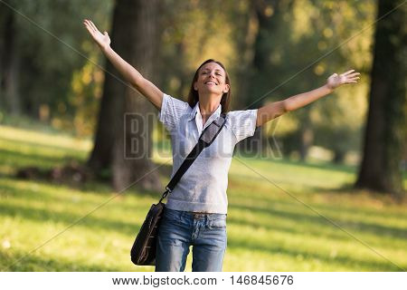 Beautiful businesswoman enjoys in the park with her arms outstreched.