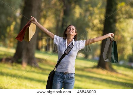 Beautiful businesswoman enjoys in the park with her arms outstreched after shopping.