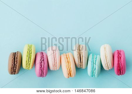 Cake macaron or macaroon on turquoise background from above. Colorful almond cookies, pastel colors. Vintage card, top view, flat lay.
