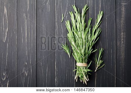 Bunch of rosemary plant on black rustic table from above, fresh herbs. Food background for menu or recipe.