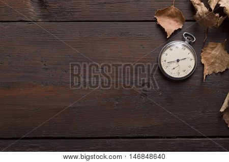 old clock on a wooden board and autumn leaves