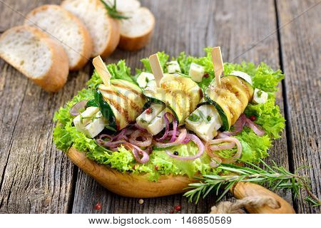 Delicious Greek appetizers: Grilled zucchini rolls with feta cheese and herbs on roasted onion rings and green salad