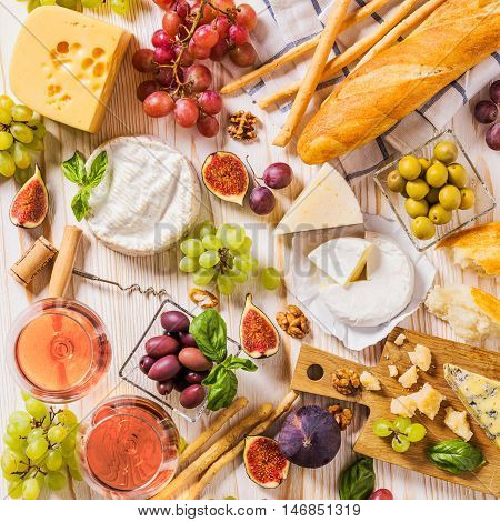 An abundance of cheese, fruits, breads, wine and snacks on white rustic table from above. French appetizer background
