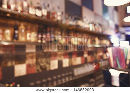 Blurred back bar. Bottles of spirits and liquor at the bar. Blurred desk in bar.