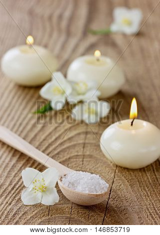 Spa composition with sea salt bath in wooden spoon, jasmine flowers and burning candles on a rustic surface. Aromatherapy concept, selective focus.