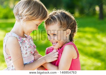 Portrait of Two Little Girlfriends / Sisters Tickling Each Other