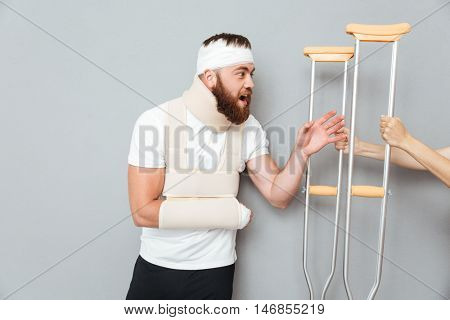 Happy excited bandaged man taking crutches from female hands over gray background