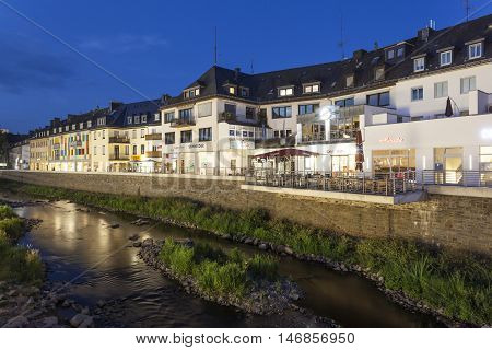 SIEGEN GERMANY - SEP 1 2016: Waterfront buildings at the Sieg river in the city of Siegen at night. North Rhine Westphalia Germany