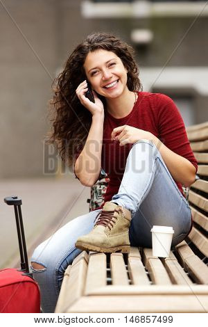 Travel Woman Sitting Outside And Taking On Cell Phone
