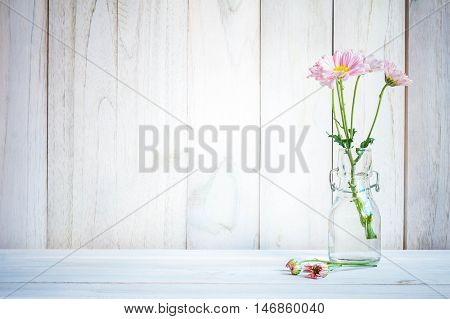 Home interior decorbouquet of pink flowers in a vase on white wood table background