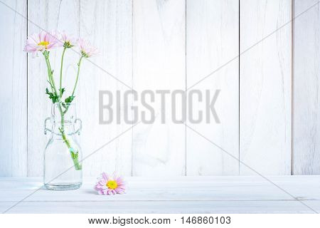 daisies in vase on a old wooden table