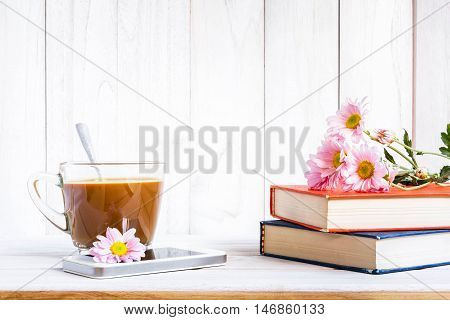 Coffee cup and books or journal with flowers arranged on a neutral white painted desk.