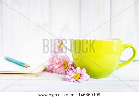 Notebook with a pencil on the table next to coffee and flowers.