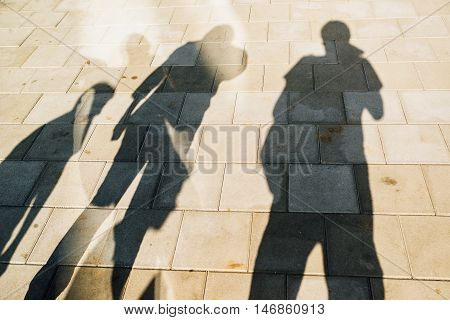 People casting shadows on the pavement four young man and women overshadowing street concrete tiles