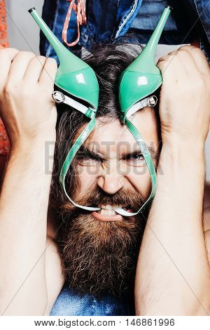 Angry man hipster with beard bites leather straps of green high heels shoes among clothes in closet