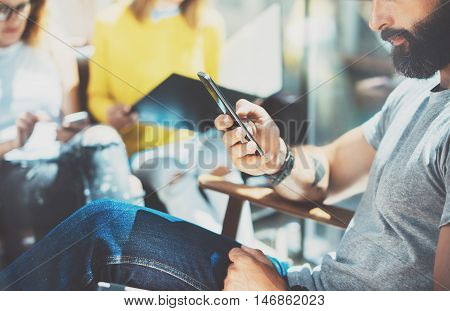 Bearded Hipster Man Using Modern Smartphone.Yound Business People Gathered Together Discussing Creative Idea City Cafe.Coworker Meeting Communication Discussion Working Office Startup Concept.Blurred