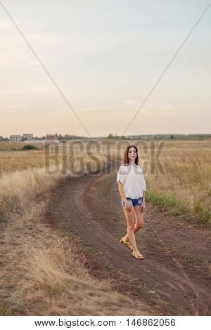 Young girl with long brown hair walking along the road in autumn field and looks happily. Selective focus warm tinted.