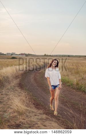 Young girl with long brown hair walking along the road in autumn field smiling and looks happily. Selective focus warm tinted.