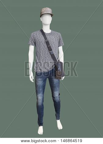 Full length male mannequin dressed in t-shirt and blue jeans isolated on green background. No brand names or copyright objects.
