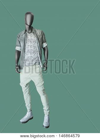 Full length male mannequin dressed in shirt t-shirt and jeans isolated on green background. No brand names or copyright objects.
