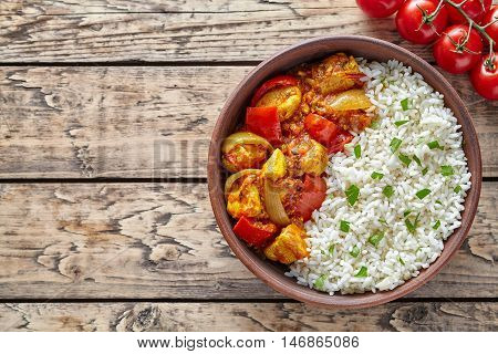 Chicken jalfrezi traditional Indian spicy curry chilli meat with basmati rice and vegetables healthy dietetic asian food in clay dish on vintage table background.