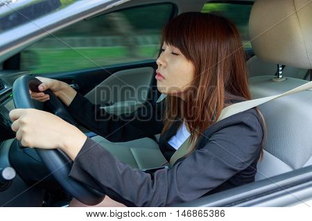 Closeup portrait sleepy tired close eyes young woman driving her car after long hour trip Sleep deprivation accident concept poster